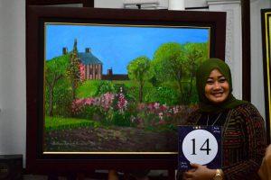 Deice Hanum Wulan, pemenang lelang berfoto bersama lukisan karya Andrew. Lukisan yang dilelang merupakan karya dari pengidap autis dan down syndrome