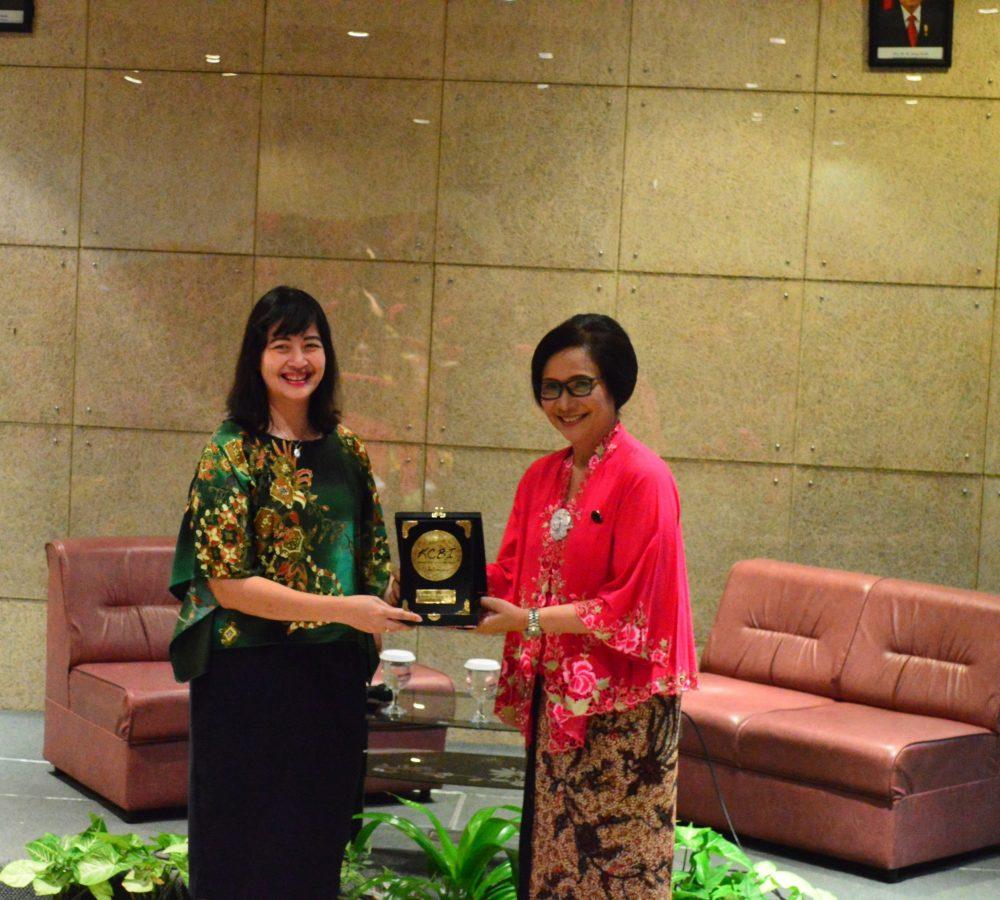 Indriana Lestari, S.Sos., M.A. (kiri) menerima pemberian cenderamata dari KCBI Surabaya