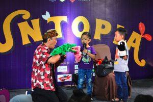 Kak Toby (kiri) bermain boneka karakter bersama dengan dua peserta Funtopia 2019