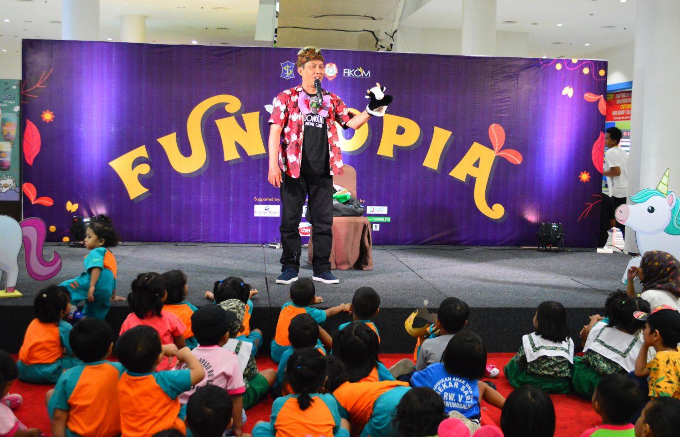 Kak Toby membawakan dongeng dengan boneka karakter pada peserta anak-anak