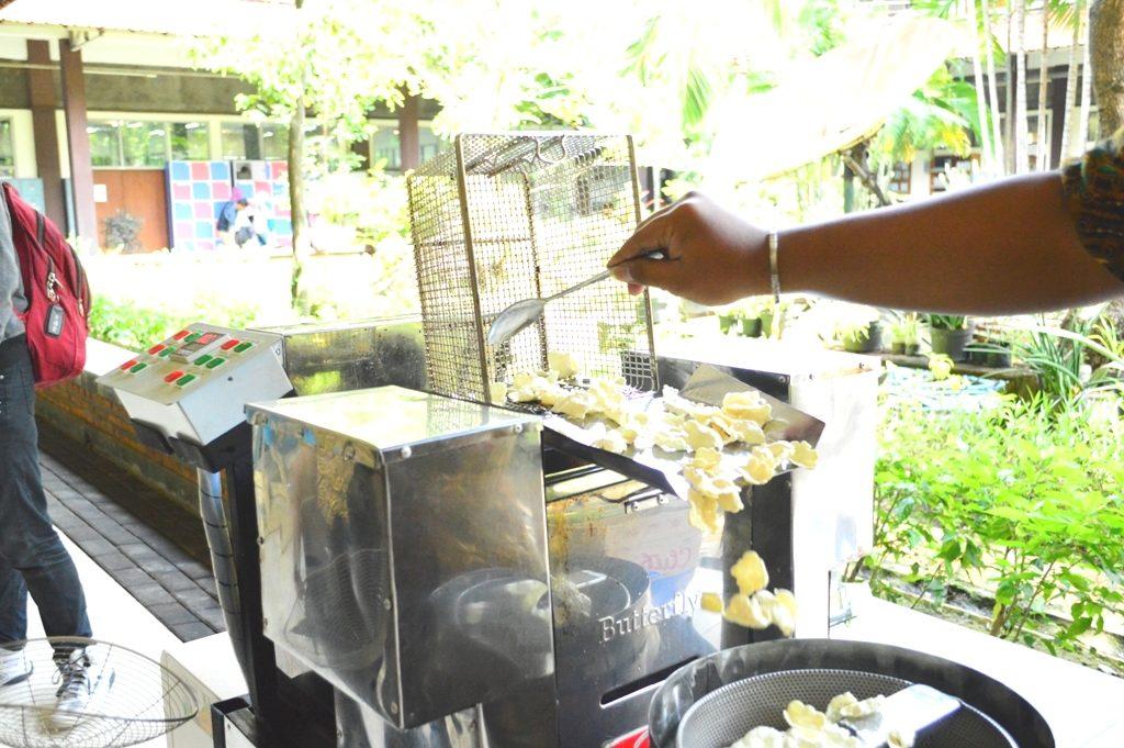 Mesin penggoreng kerupuk secara otomatis mengangkat hasil jadi kerupuk dan dimasukkan ke bagian penirisan