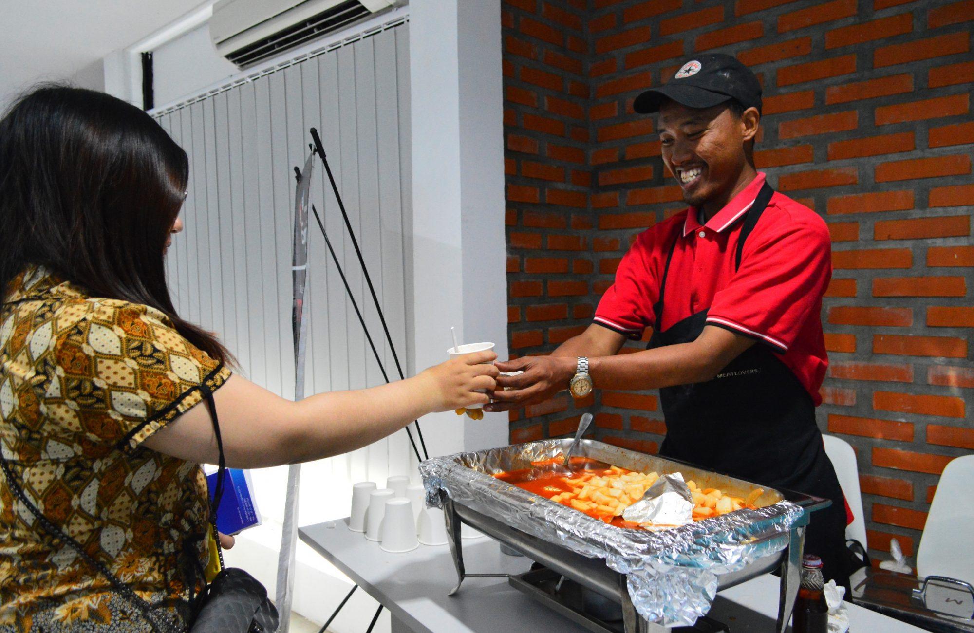 Pengunjung menikmati tteokbokki, makanan ringan ringan khas Korea secara gratis.