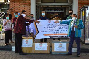 Peter Manuputty (kiri) dari Perwakilan Masyarakat Maluku Surabaya menerima bantuan APD untuk RS. Dr Haulussy Ambon dari Dekan Fakultas Kedokteran UKWMS, Prof. Dr. Paul Tahalele (kanan)