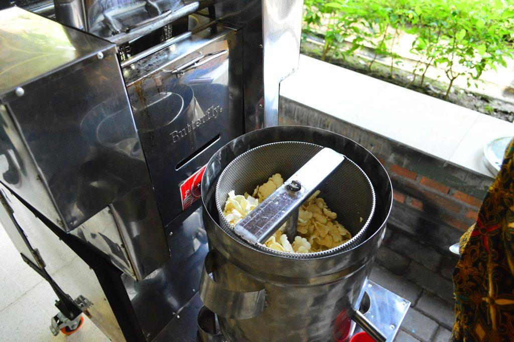 Proses meniriskan minyak dari kerupuk yang telah digoreng sehingga siap dikemas