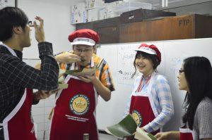 Dua orang mahasiswa NTUST Taiwan mencoba memakan nasi tumpeng dengan menggunakan alas pincuk dan suru sebagai sendok