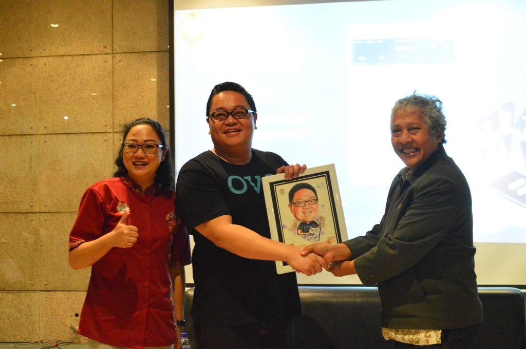 Pemberian cinderamata berupa karikatur oleh Wakil Rektor III UKWMS, Drs. J.V. Djoko Wirjawan, Ph.D. kepada Direktur OVO, Johnny Widodo.